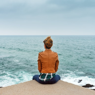 woman in brown jacket sitting on brown rock near sea during daytime