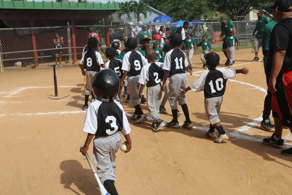 group of men playing baseball during daytime