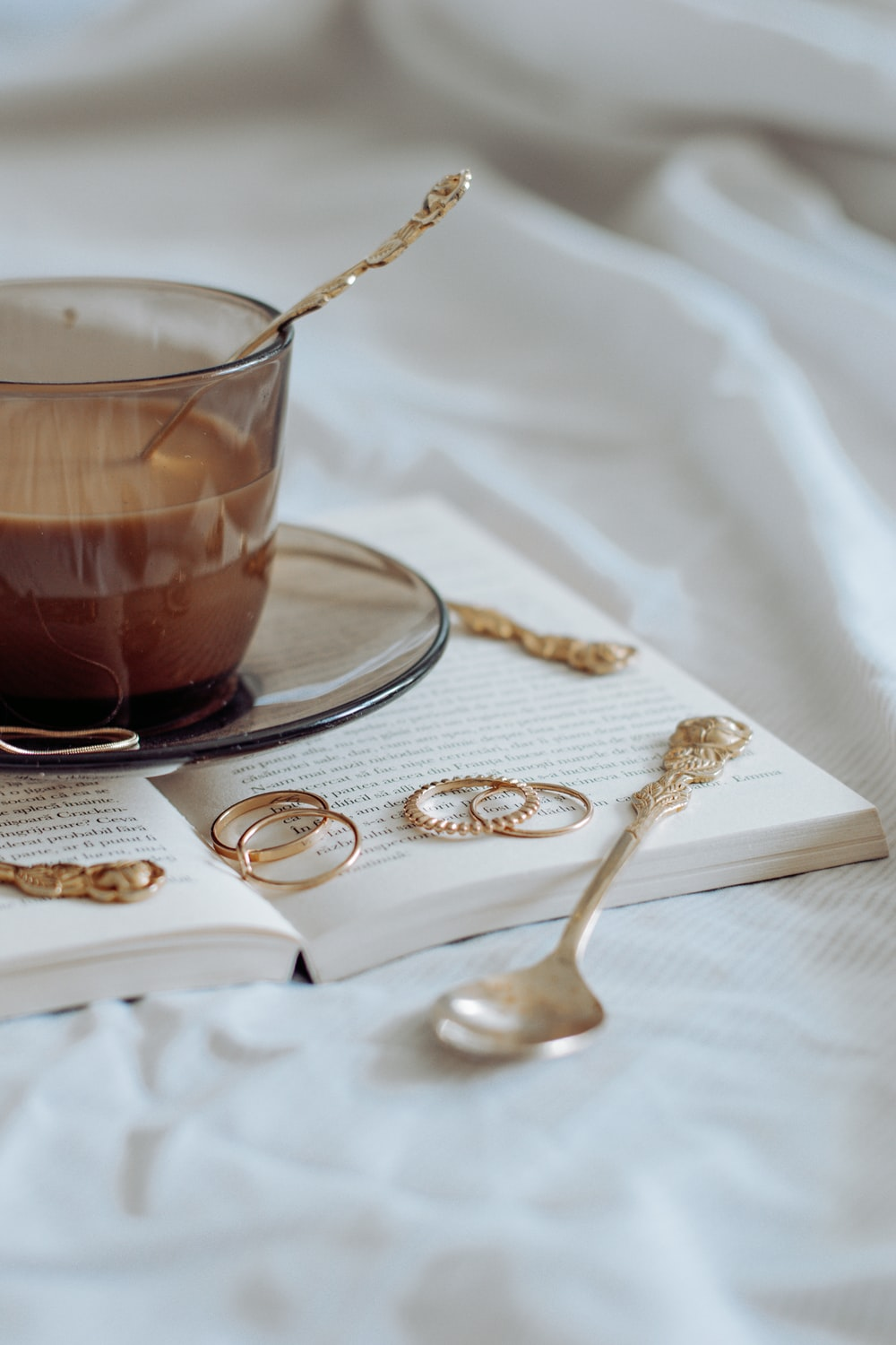 clear glass teacup on saucer with silver spoon