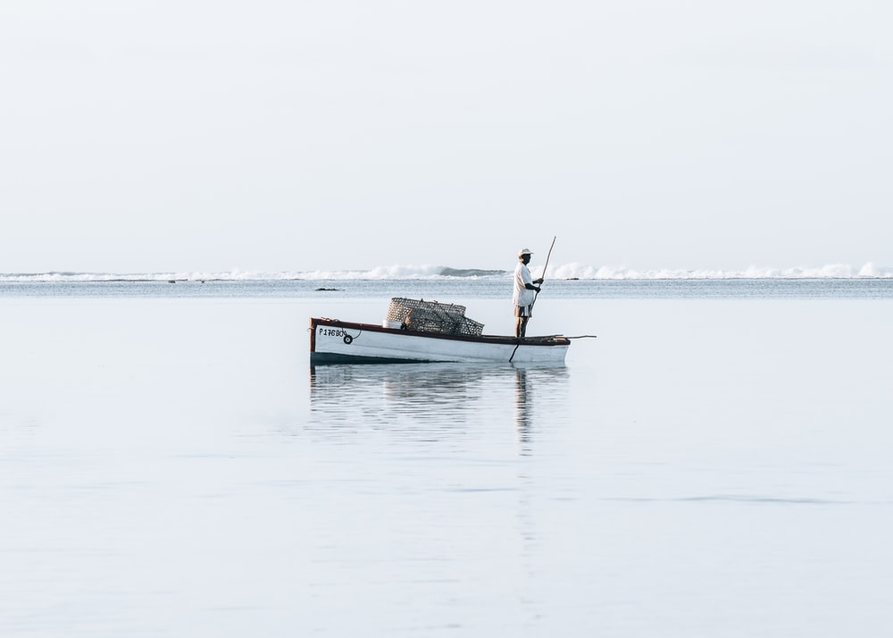 man in boat on sea during daytime