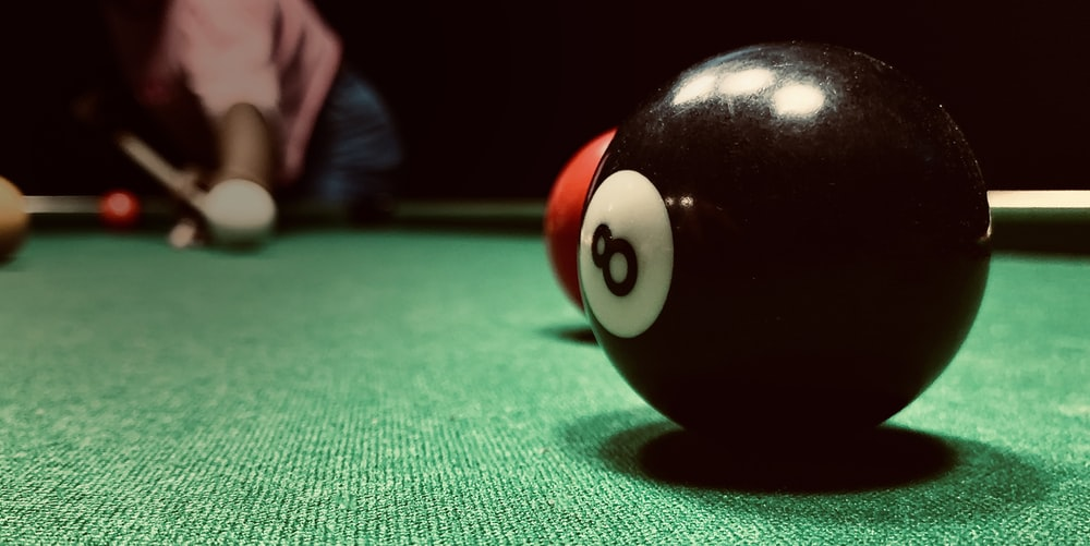 black billiard ball on green textile