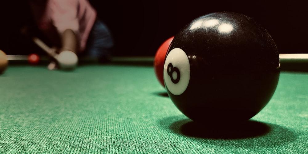 black billiard ball on green textile