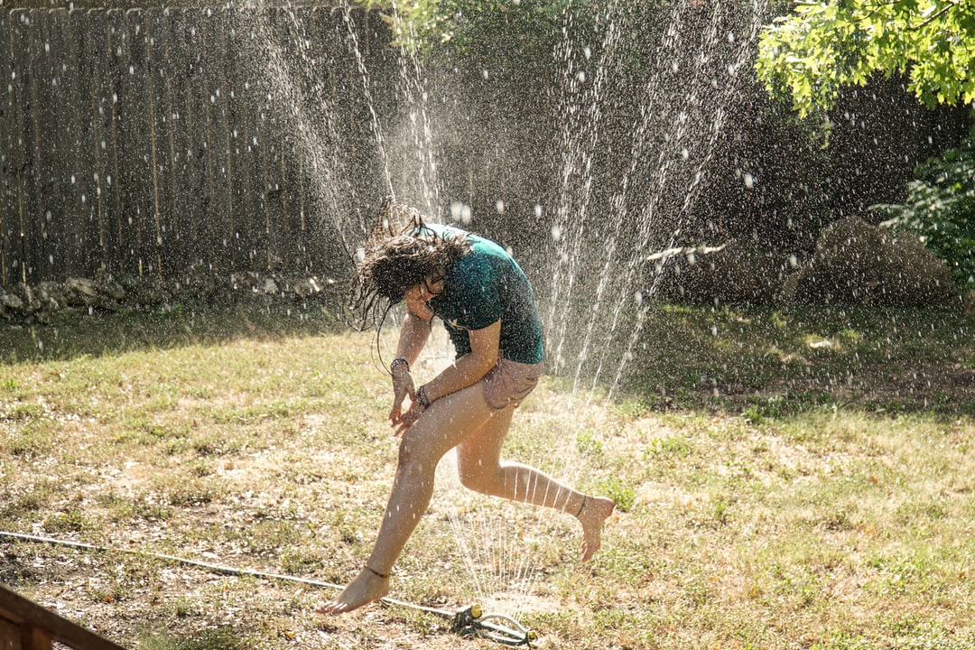 Teenage girl jumping over a water sprinkler through water on a hot summer day
