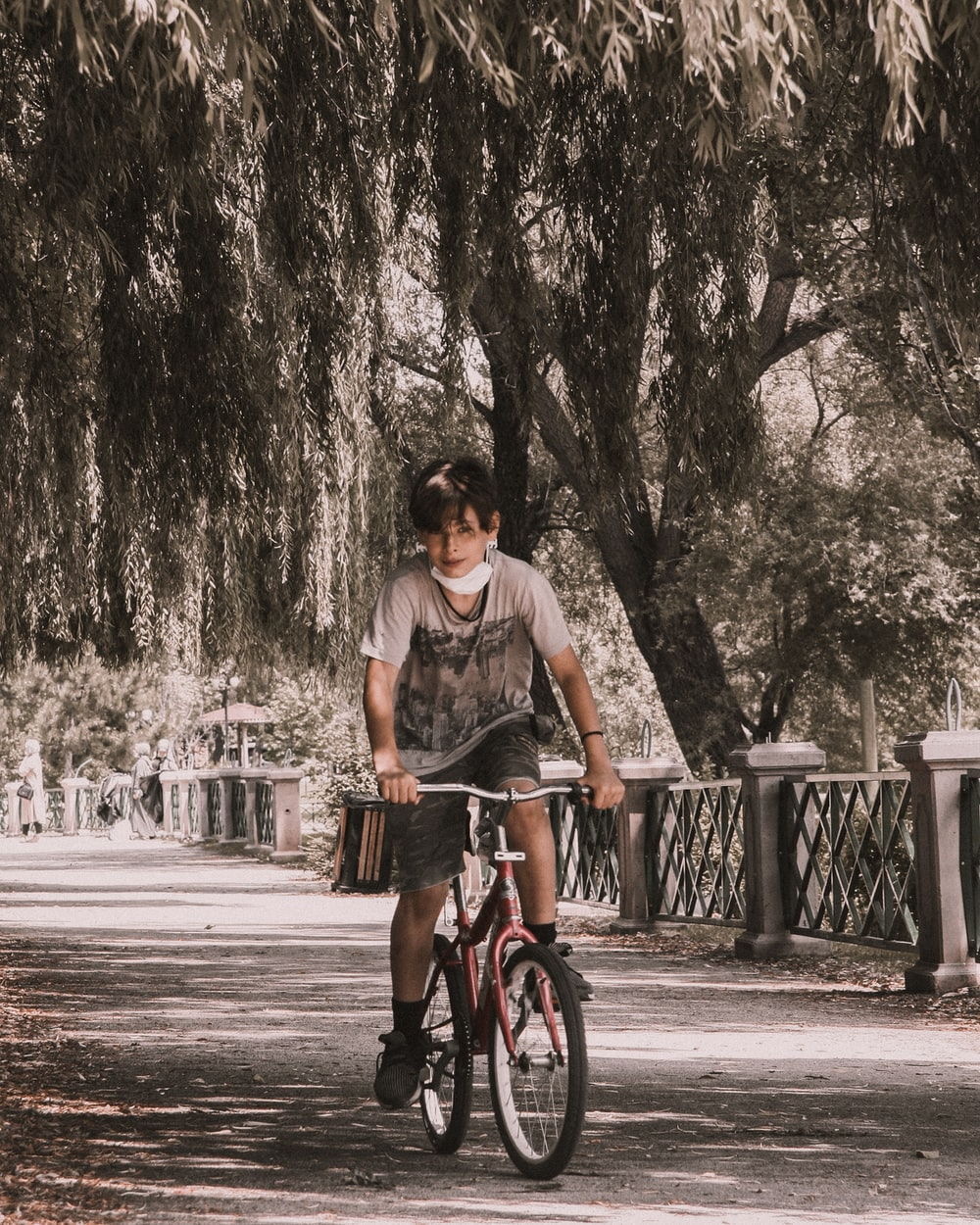 woman in black tank top riding bicycle on road during daytime