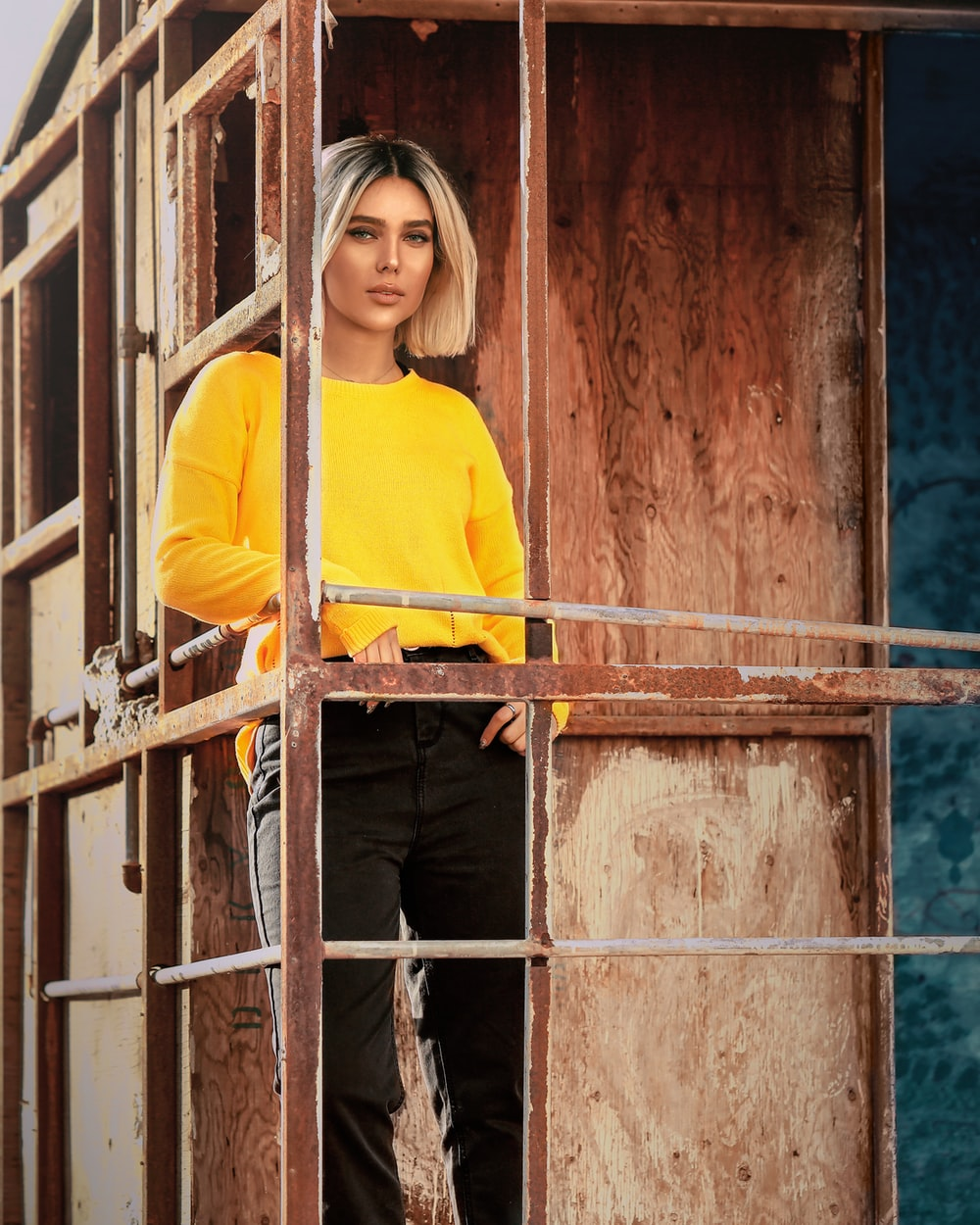 woman in yellow long sleeve shirt standing beside brown metal fence during daytime