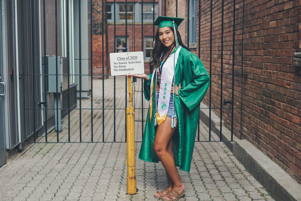 woman in green academic dress standing on sidewalk during daytime