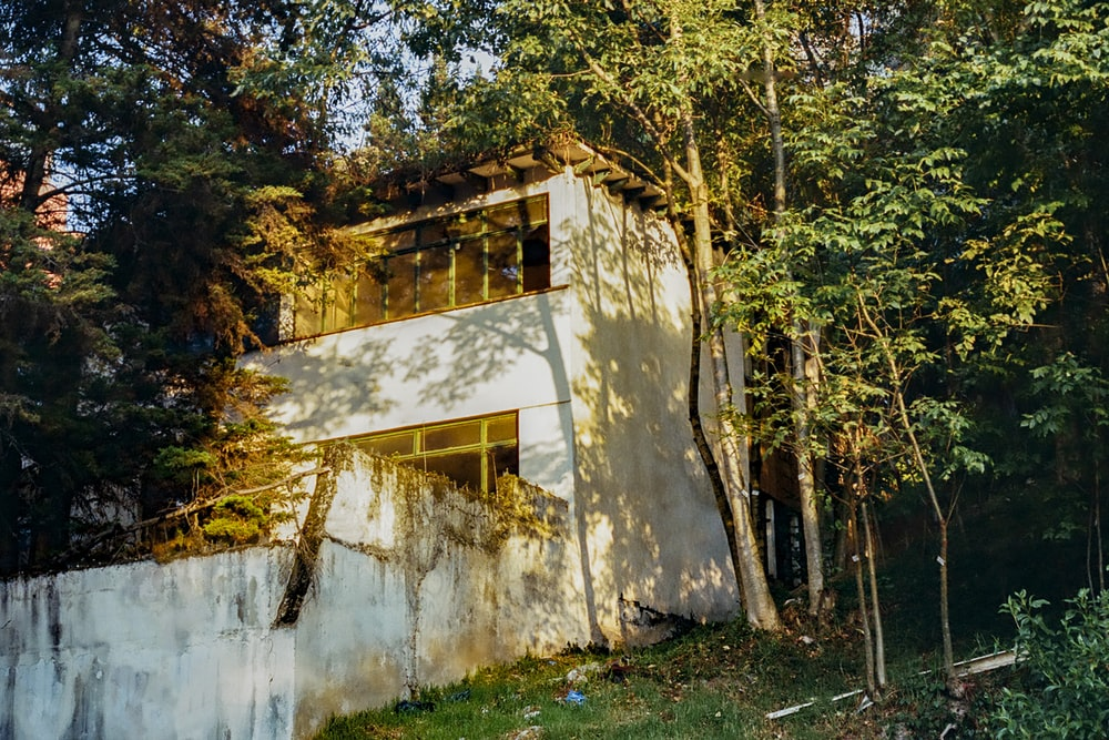 white concrete house surrounded by green trees during daytime
