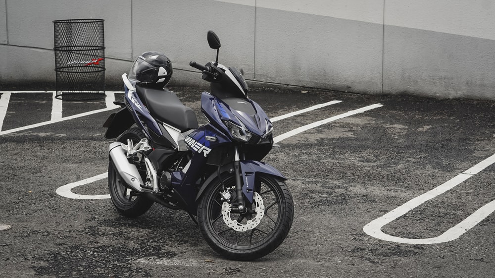 blue and black sports bike parked beside gray concrete wall