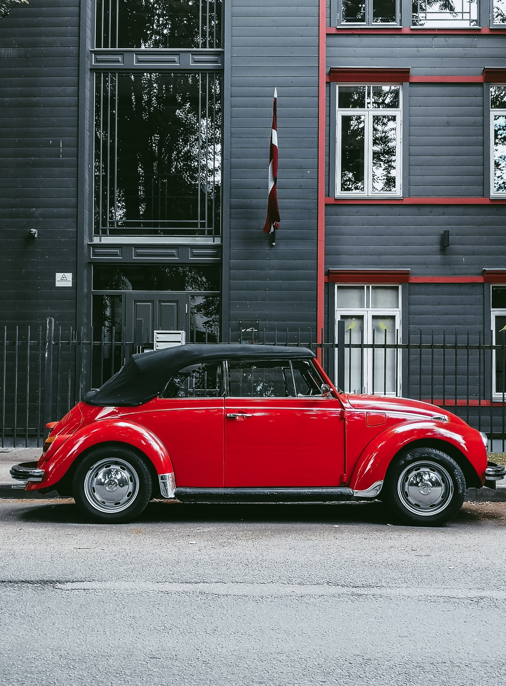 red car parked beside white and gray house