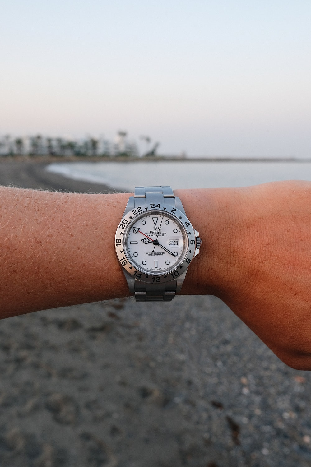 person wearing silver link bracelet round analog watch