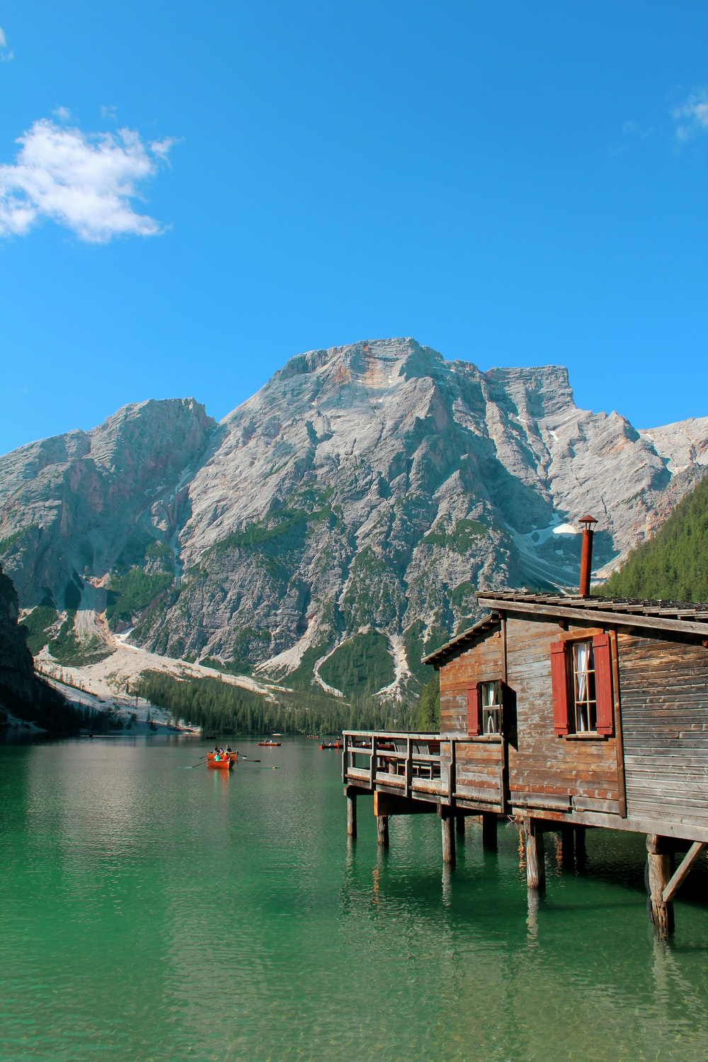 brown wooden house on lake dock near mountain under blue sky during daytime