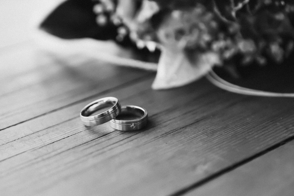 silver wedding band on wooden table