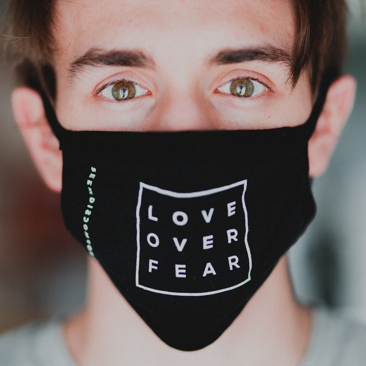 white male wearing a mask that says Love Over Fear