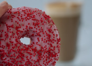 person holding doughnut with red and white sprinkles