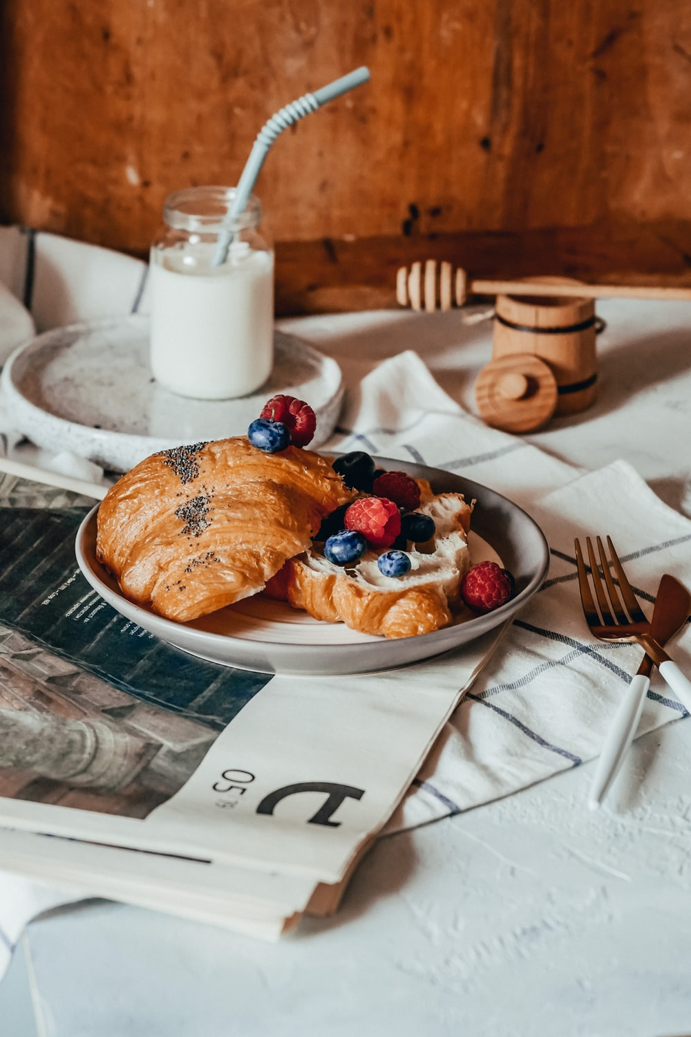 bread on white ceramic plate beside stainless steel fork and knife