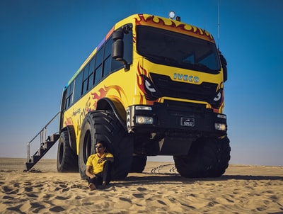 yellow school bus on gray sand during daytime qatar teams background