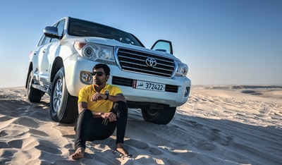 woman in yellow shirt and black pants sitting on white mercedes benz car qatar teams background