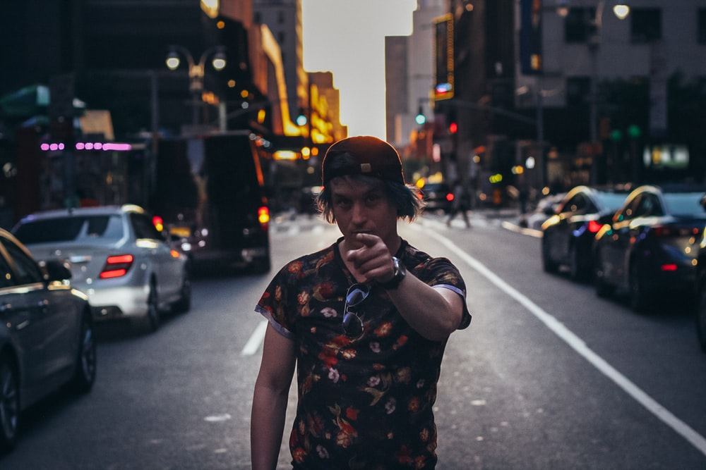 man in black and white floral shirt standing on sidewalk during night time