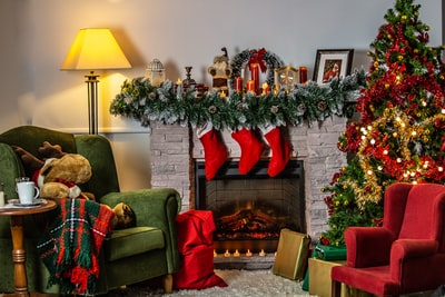 green sofa chair beside green christmas tree stocking teams background
