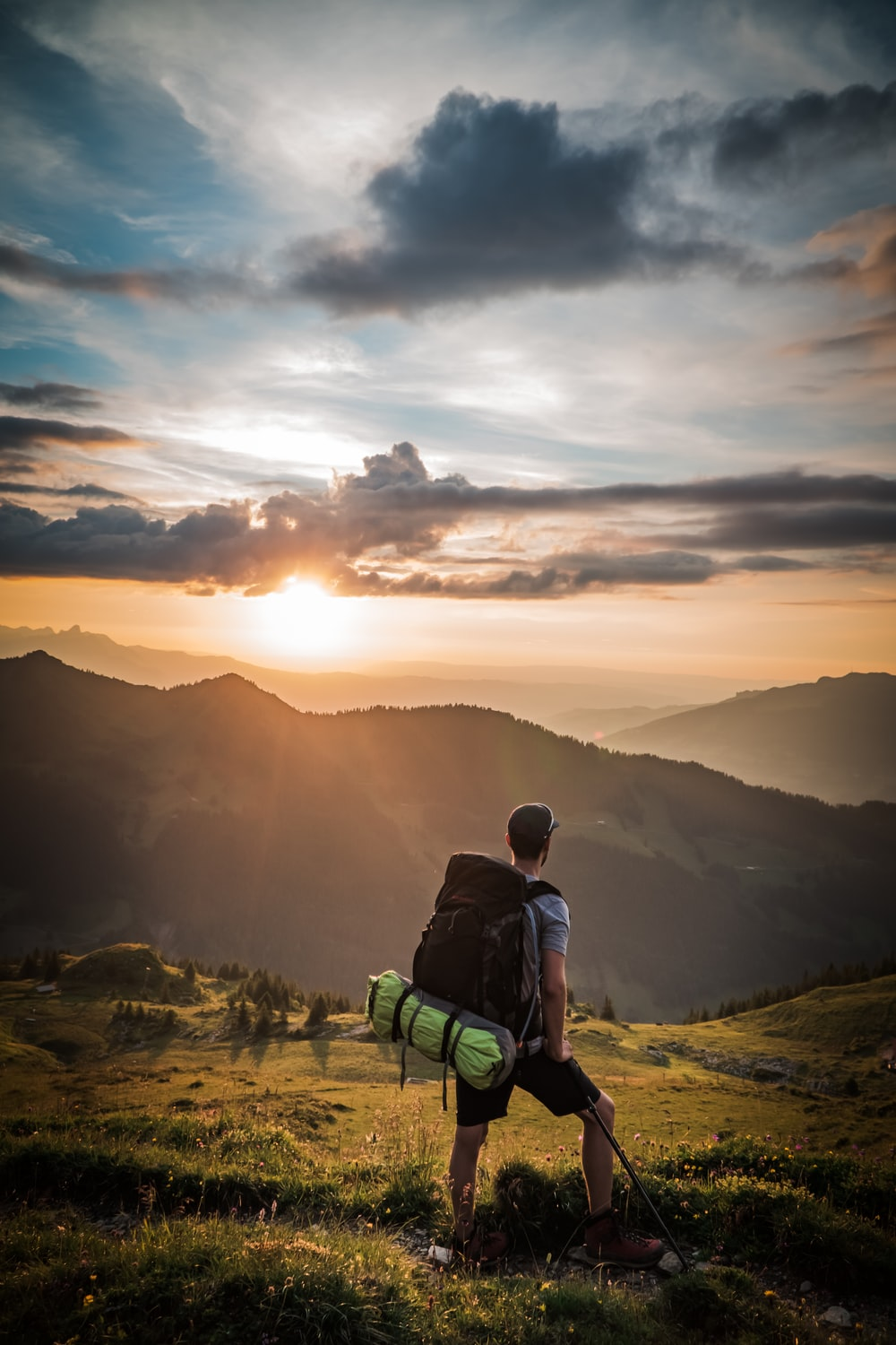 man sitting on green bench looking at the mountains during sunset