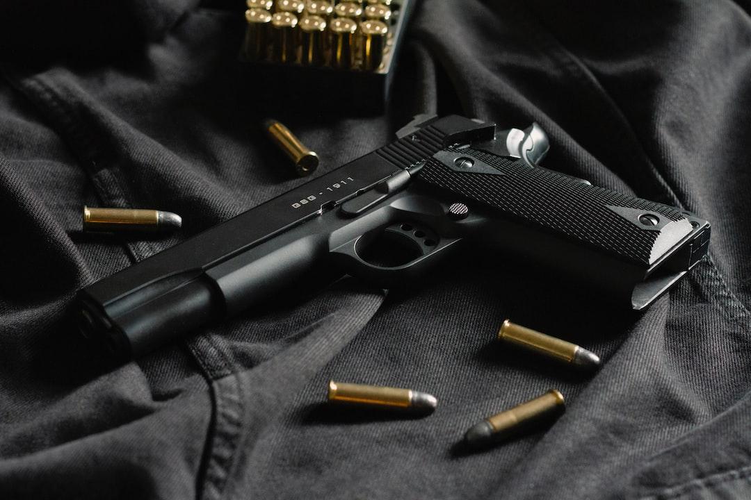 A black handgun on black cloth, with ammunition