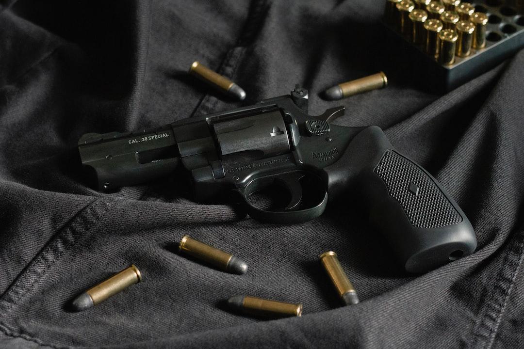 A black revolver on black cloth, with ammunition
