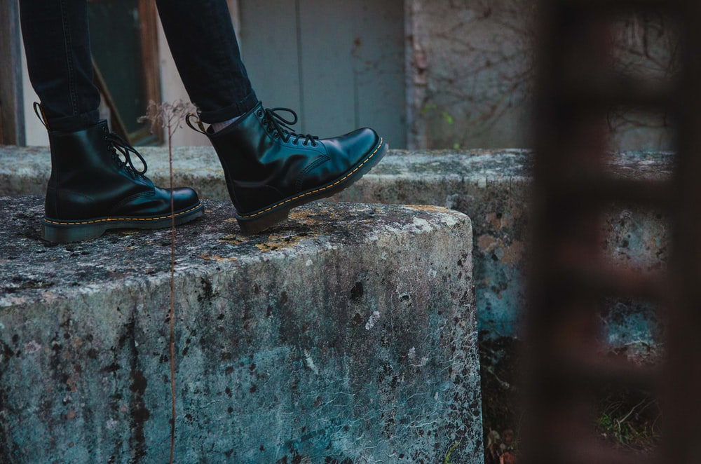 person in black leather shoes standing on gray concrete wall