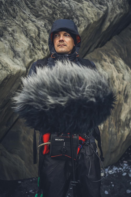 man in black fur coat standing near gray rock
