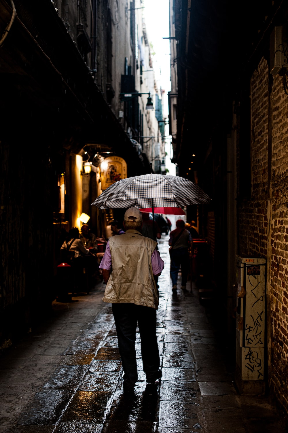 person in white coat holding umbrella walking on sidewalk during night time