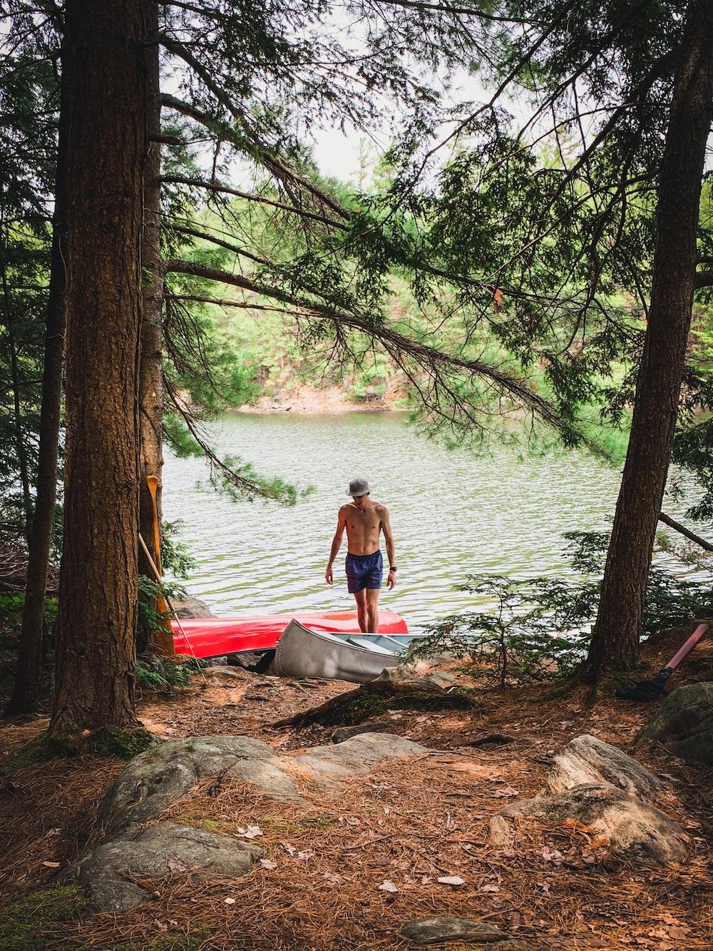 woman in black tank top sitting on red kayak on lake during daytime