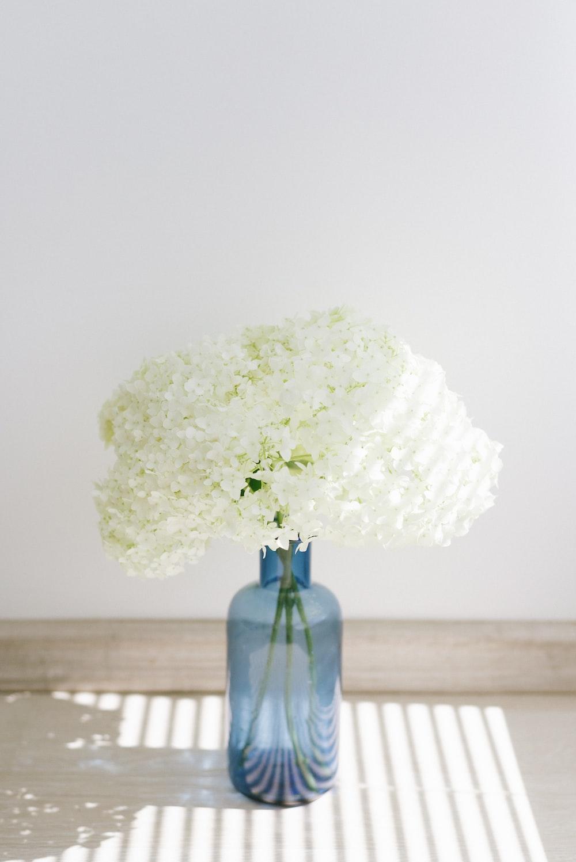 white flower on blue glass vase