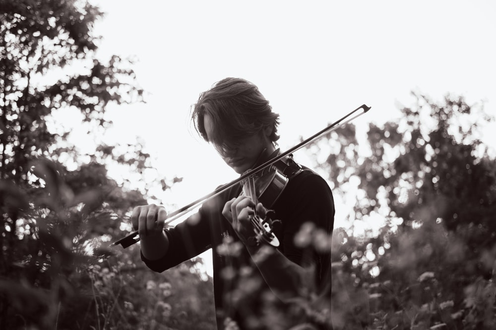 girl playing violin in grayscale photography