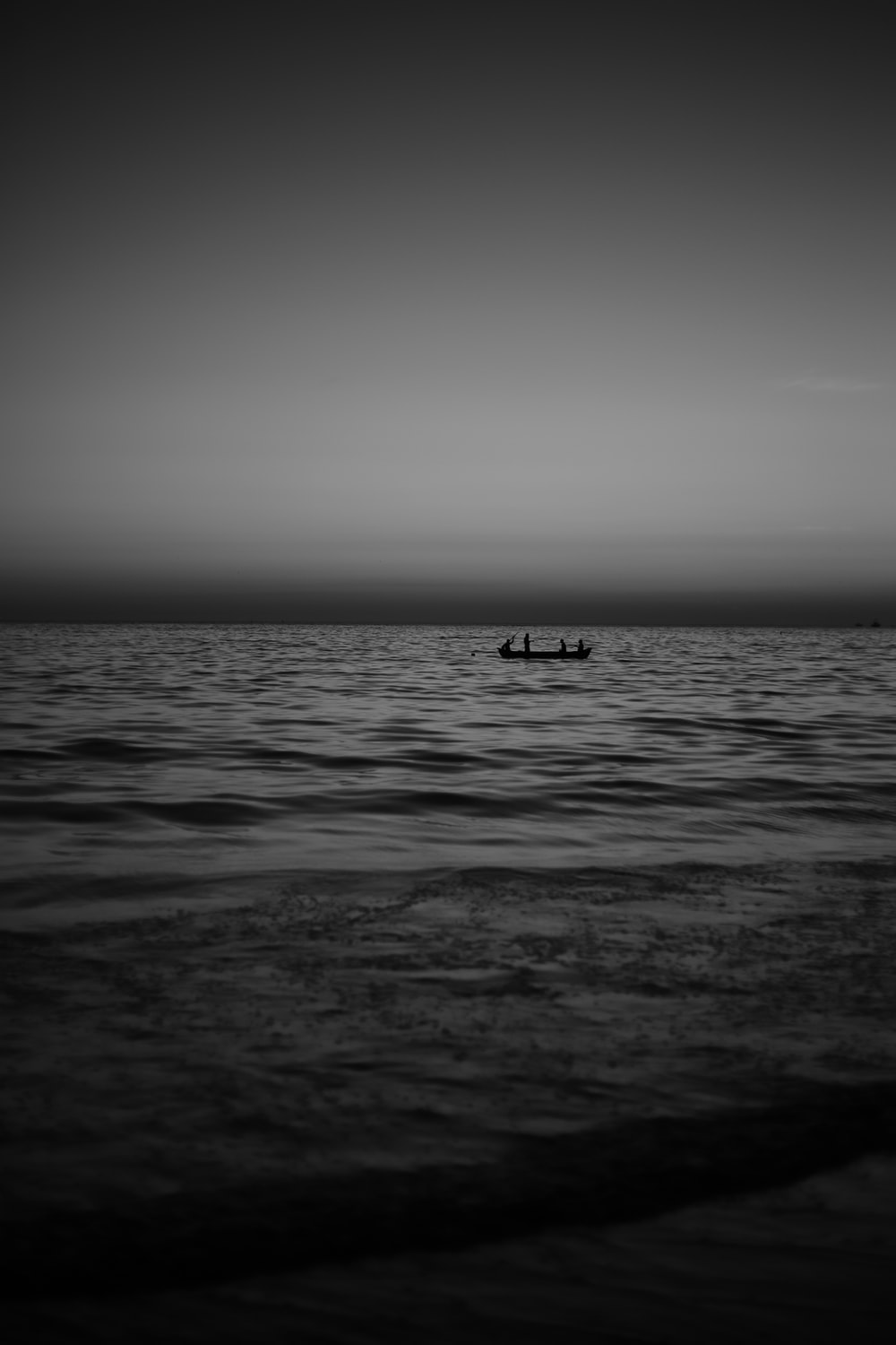 grayscale photo of person riding on boat on sea