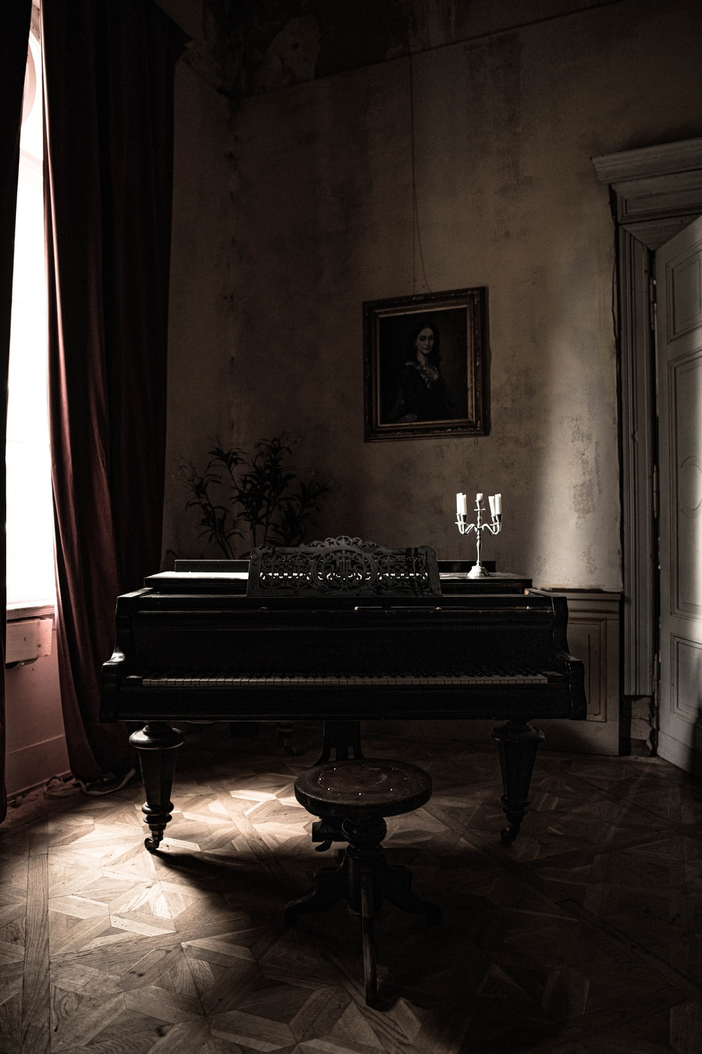 black grand piano near red curtain