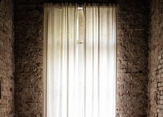 white ceramic bathtub near white window curtain