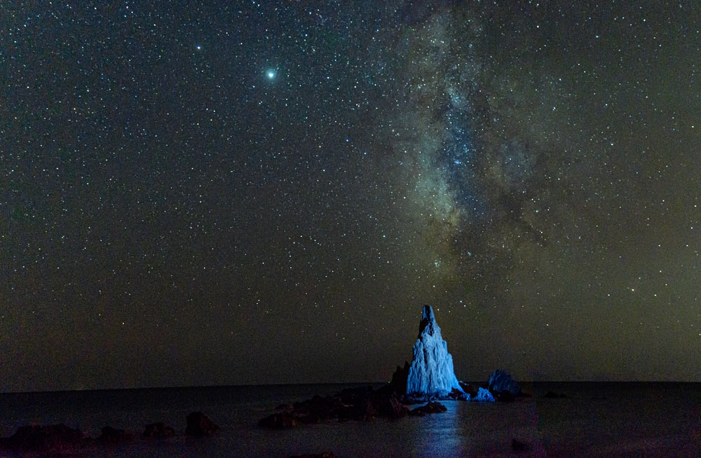 white and black rock formation under starry night