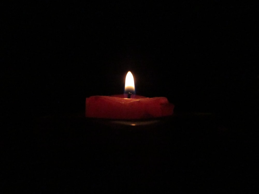 red lighted candle on dark room