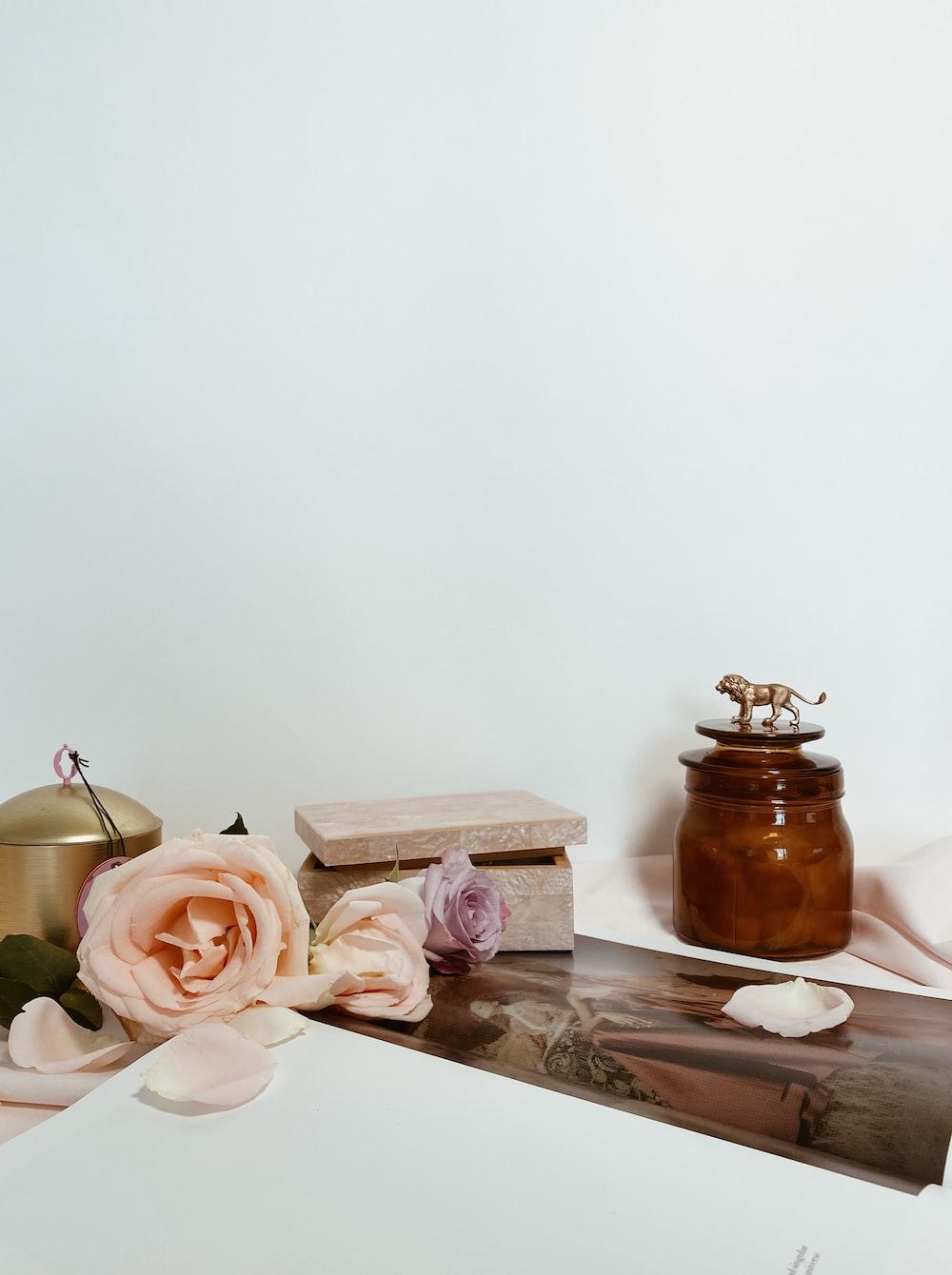 pink roses beside brown jar