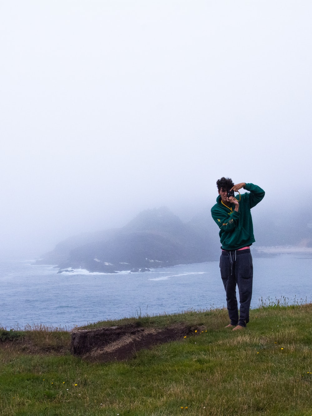 man in green hoodie standing on green grass field near body of water during daytime