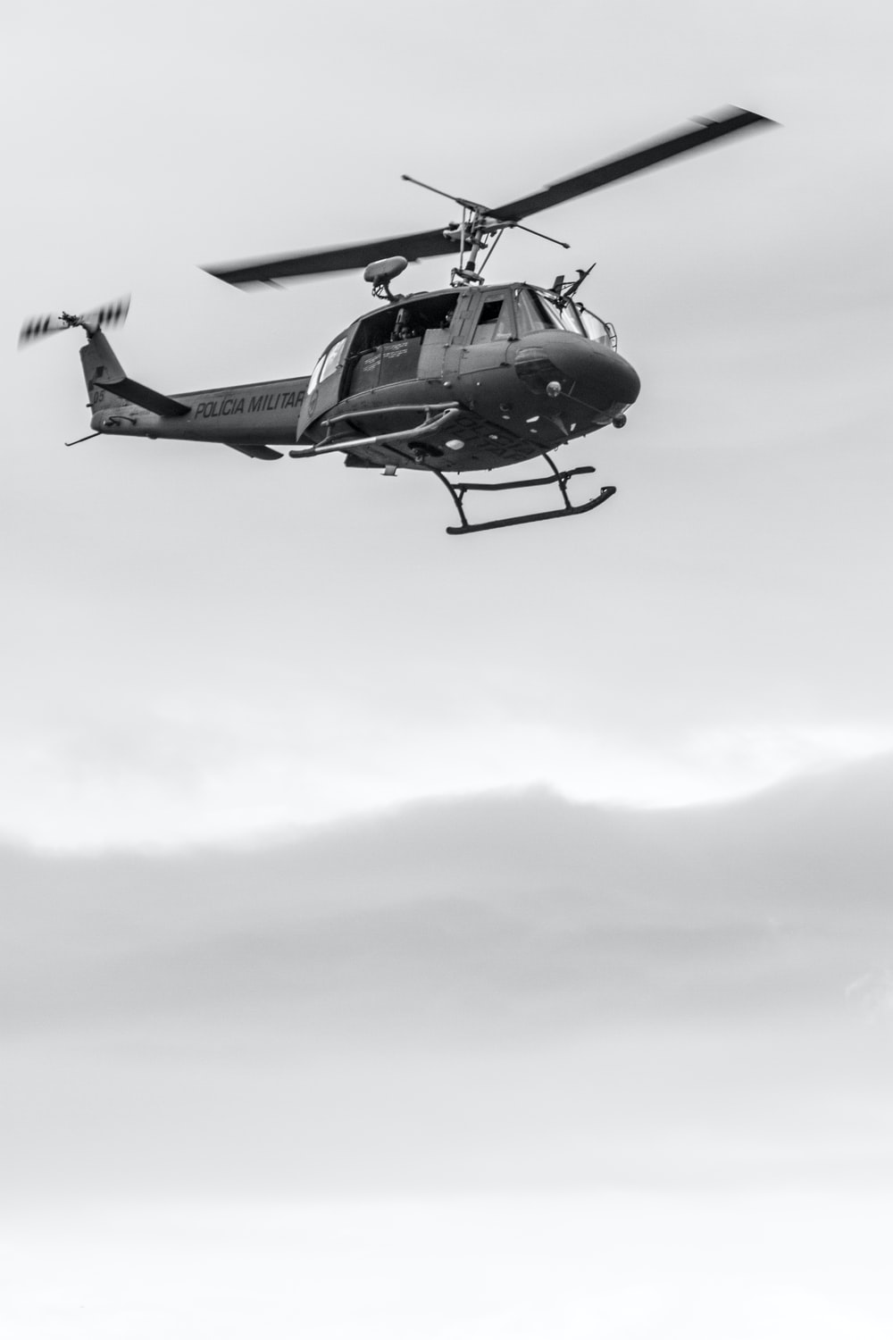 black and white helicopter flying under white clouds during daytime
