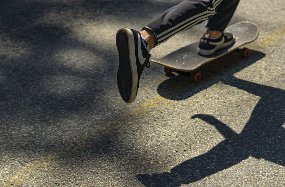 person in black and red sneakers riding skateboard