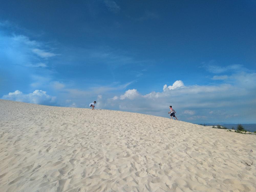people walking on sand under blue sky during daytime