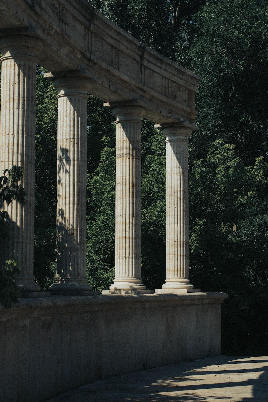 white concrete pillar near green trees during daytime
