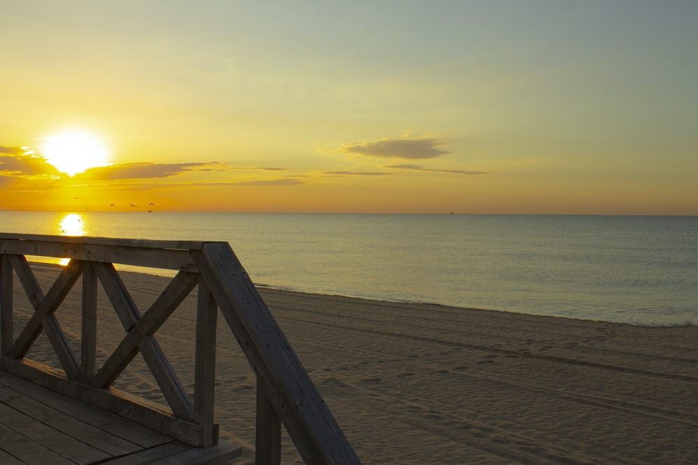 brown wooden dock on beach during sunset