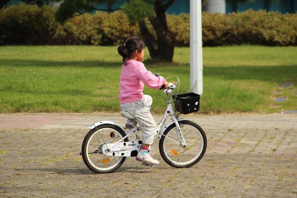 girl in pink jacket riding bicycle during daytime
