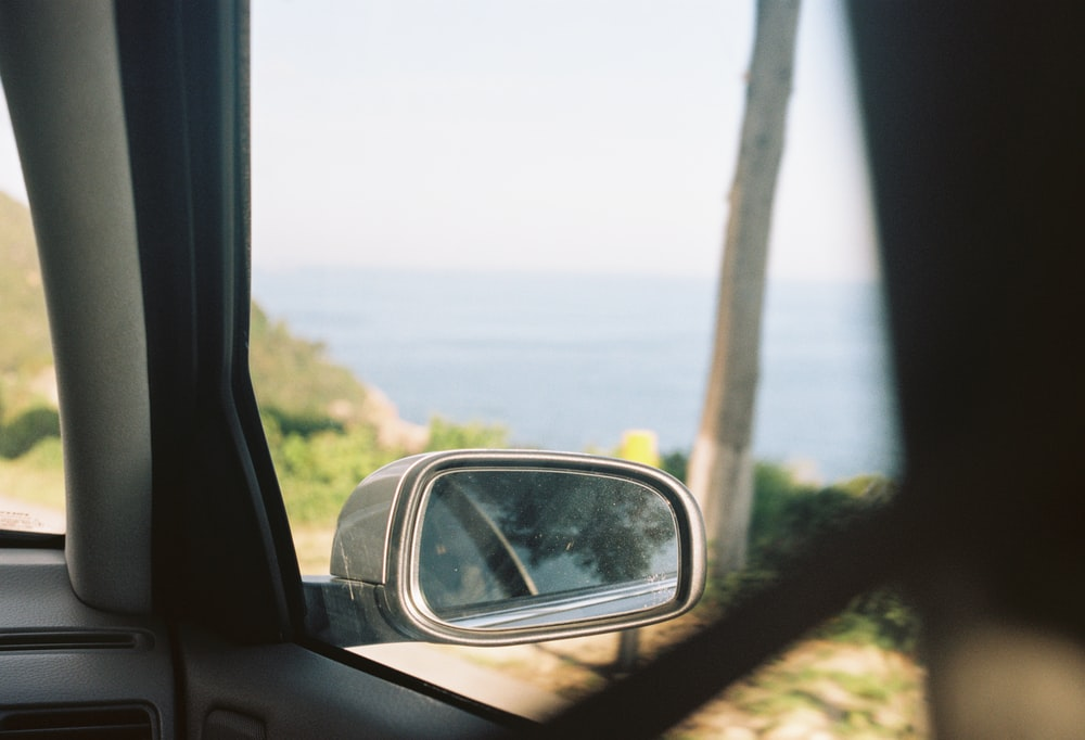 car side mirror showing green grass field during daytime