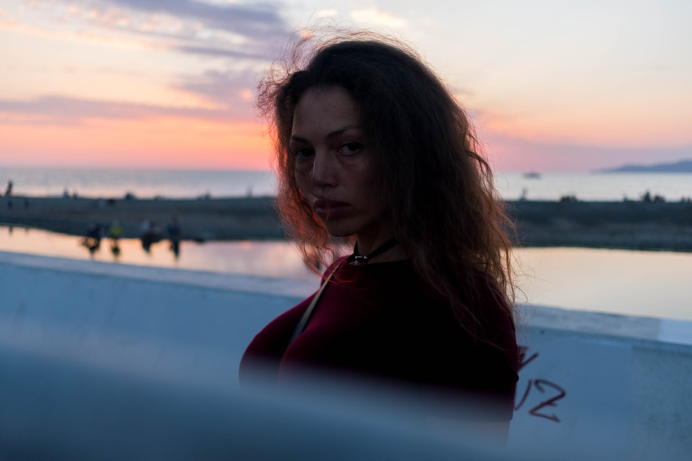 woman in red hoodie standing near body of water during daytime