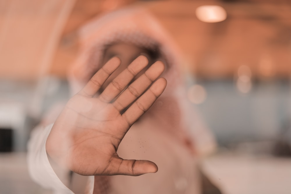 person in white long sleeve shirt covering face with hand