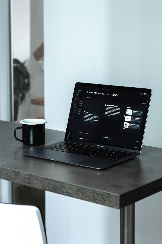 black laptop computer beside white ceramic mug on table