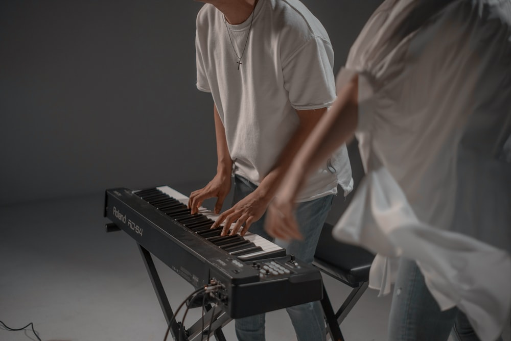 man in white crew neck t-shirt playing black electric piano